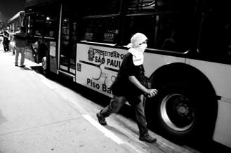 Foto de protestante ao lado de ônibus em São Paulo